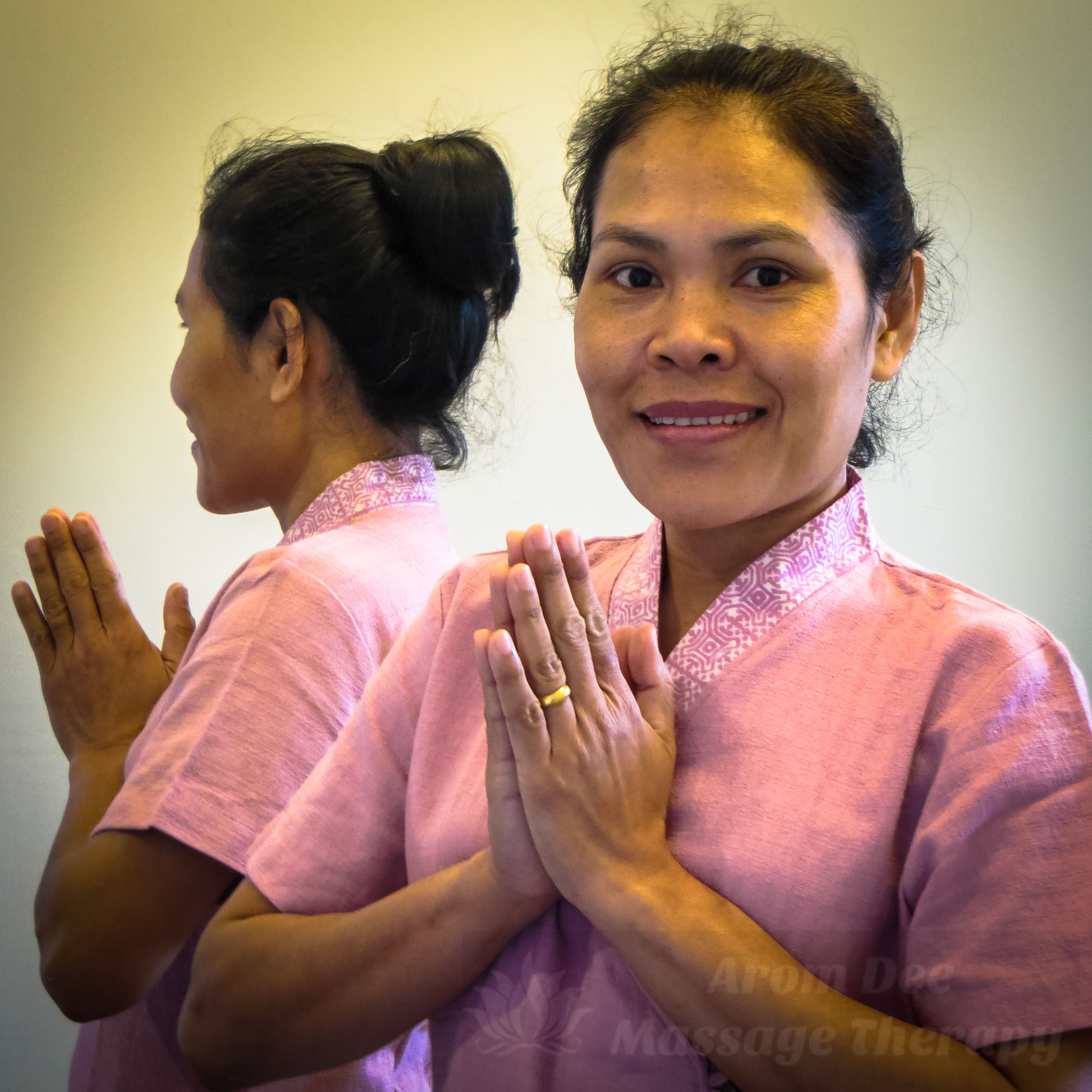 Female Thai Massage therapist wearing pink tunic making Wai with hands together