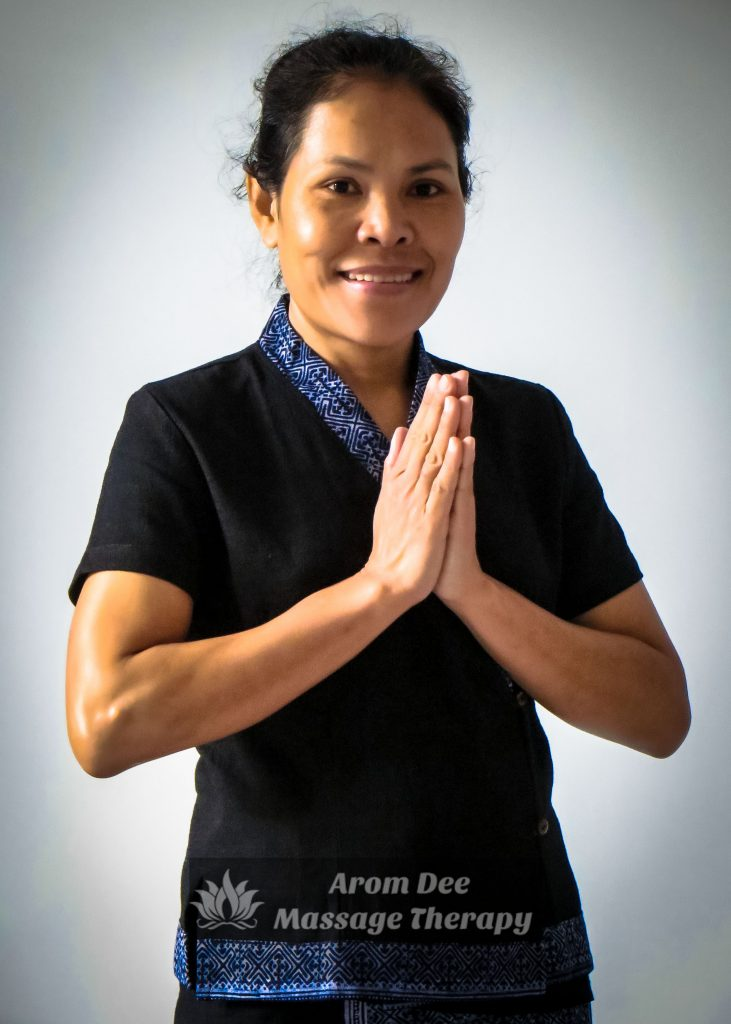 Thai Wai Massage Therapist with the palms pressed together in a prayer-like fashion wearing traditional Thai masseuse uniform