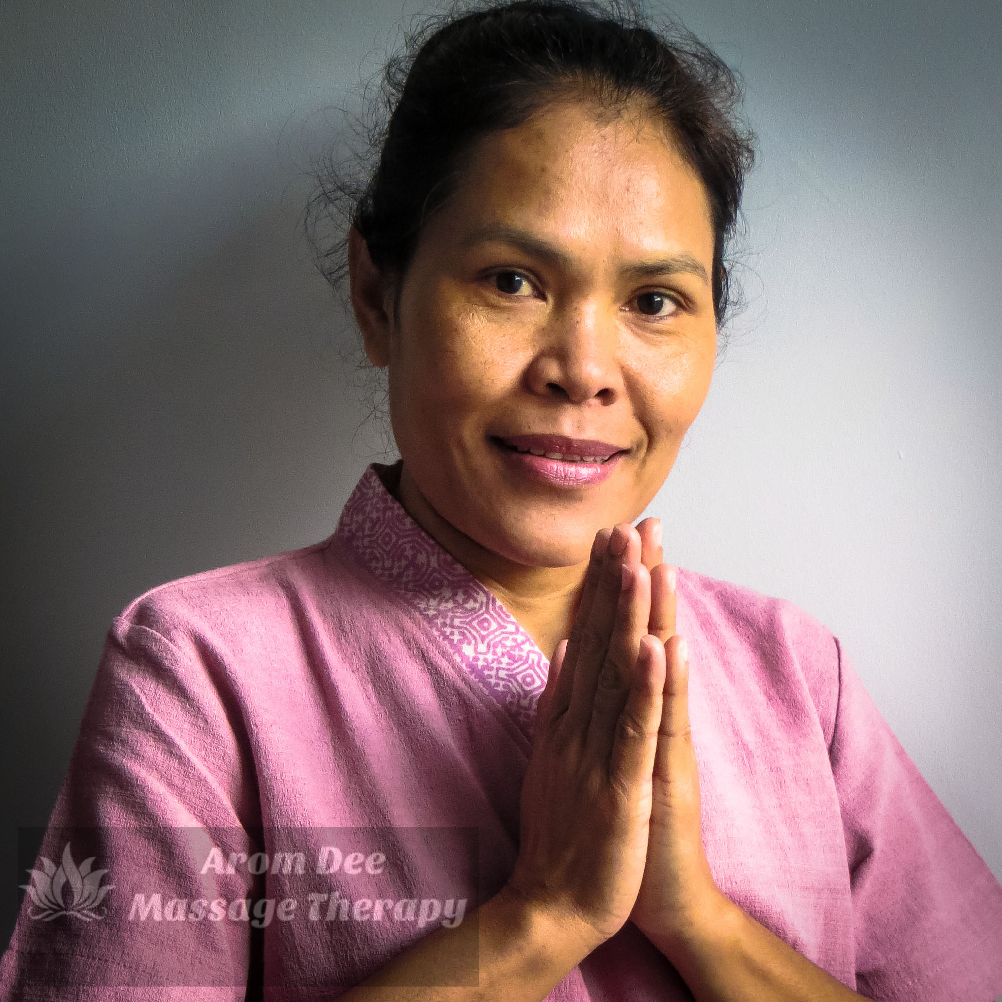 Traditional Thai therapist wearing pink tunic with both hands clasped together in front as if in prayer