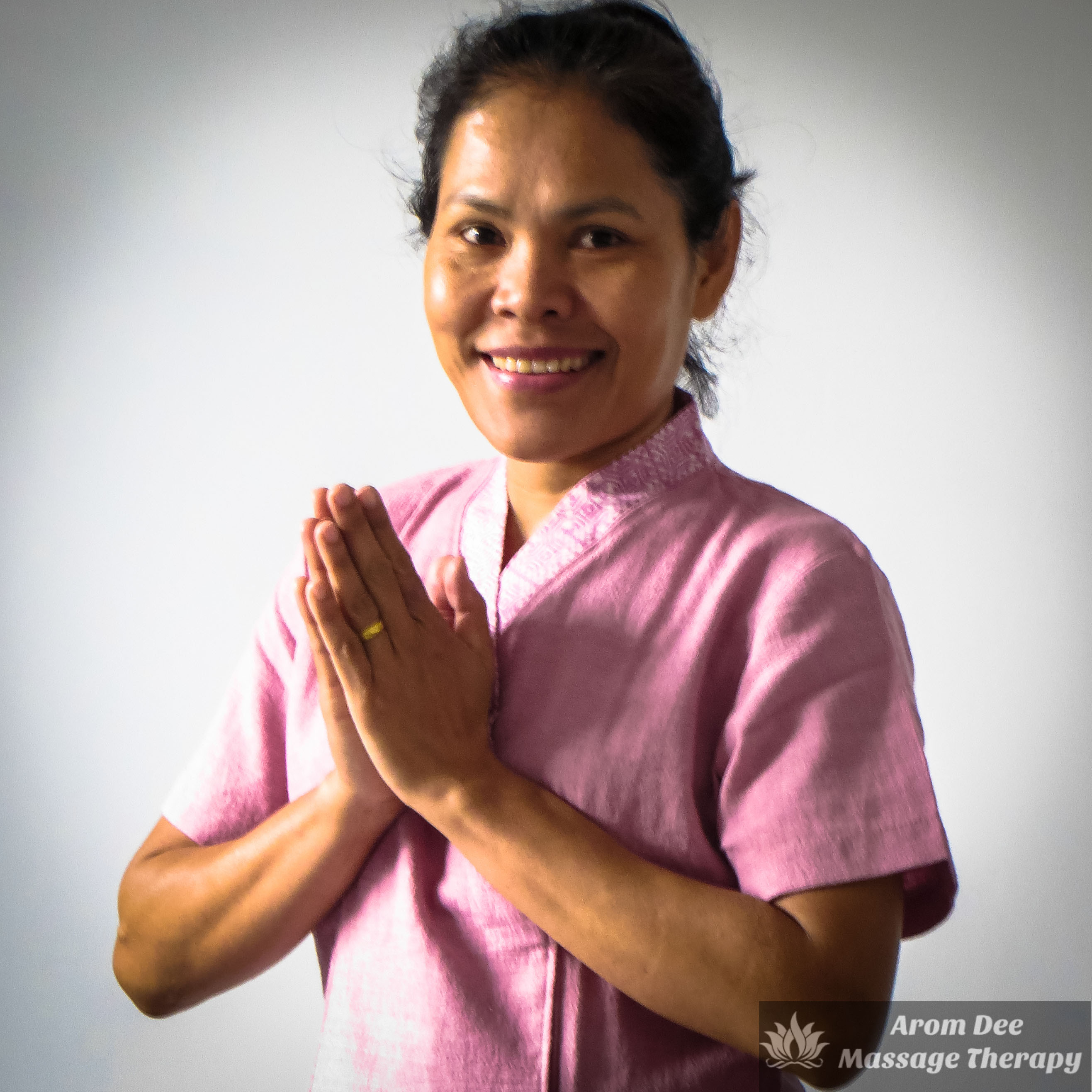Massuse wearing pink traditional massage therapist's tunic holding hands together in Thai Wai