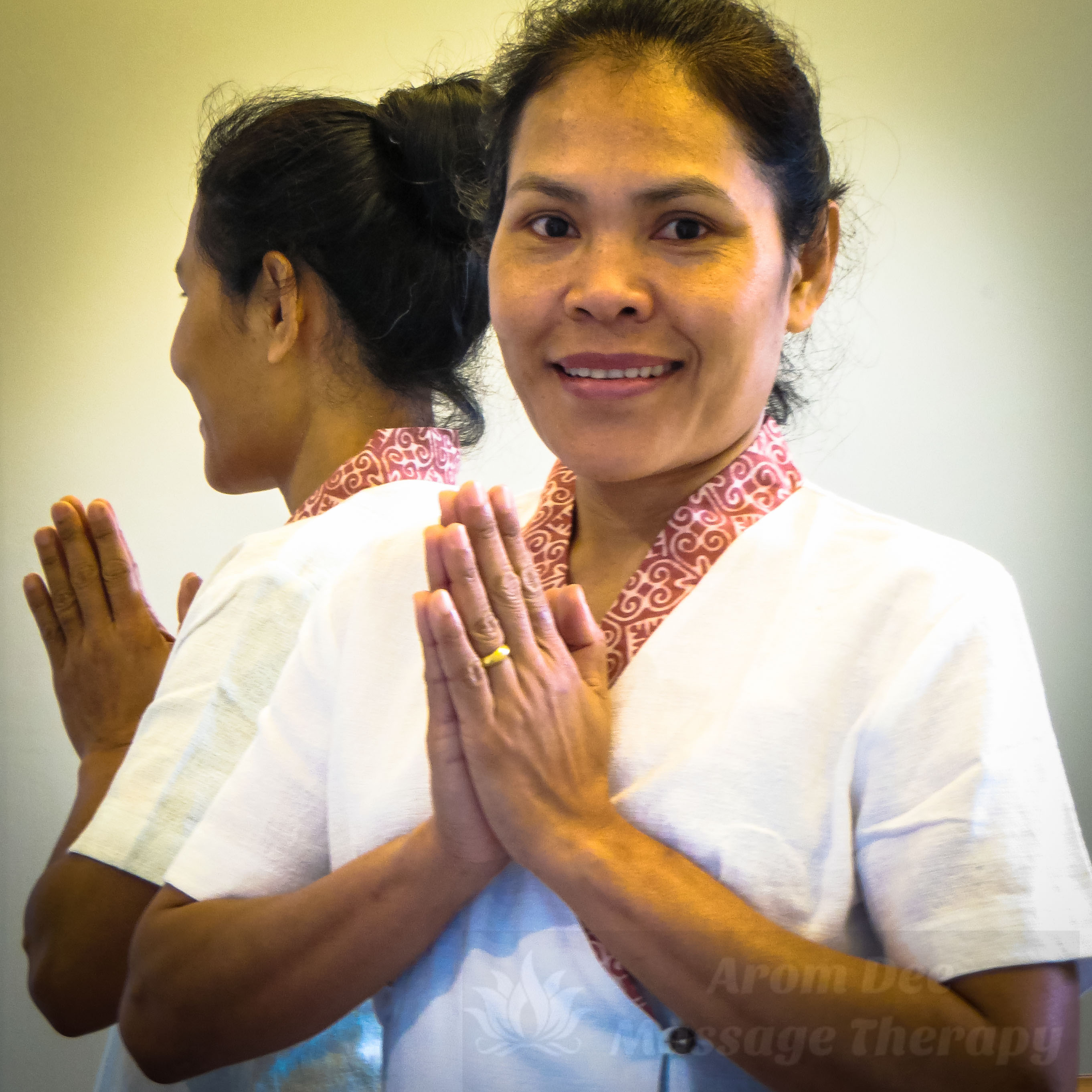 Masseuse wearing white Thai style massage therapist's tunic holdin hands together at heart level in Thai Wai