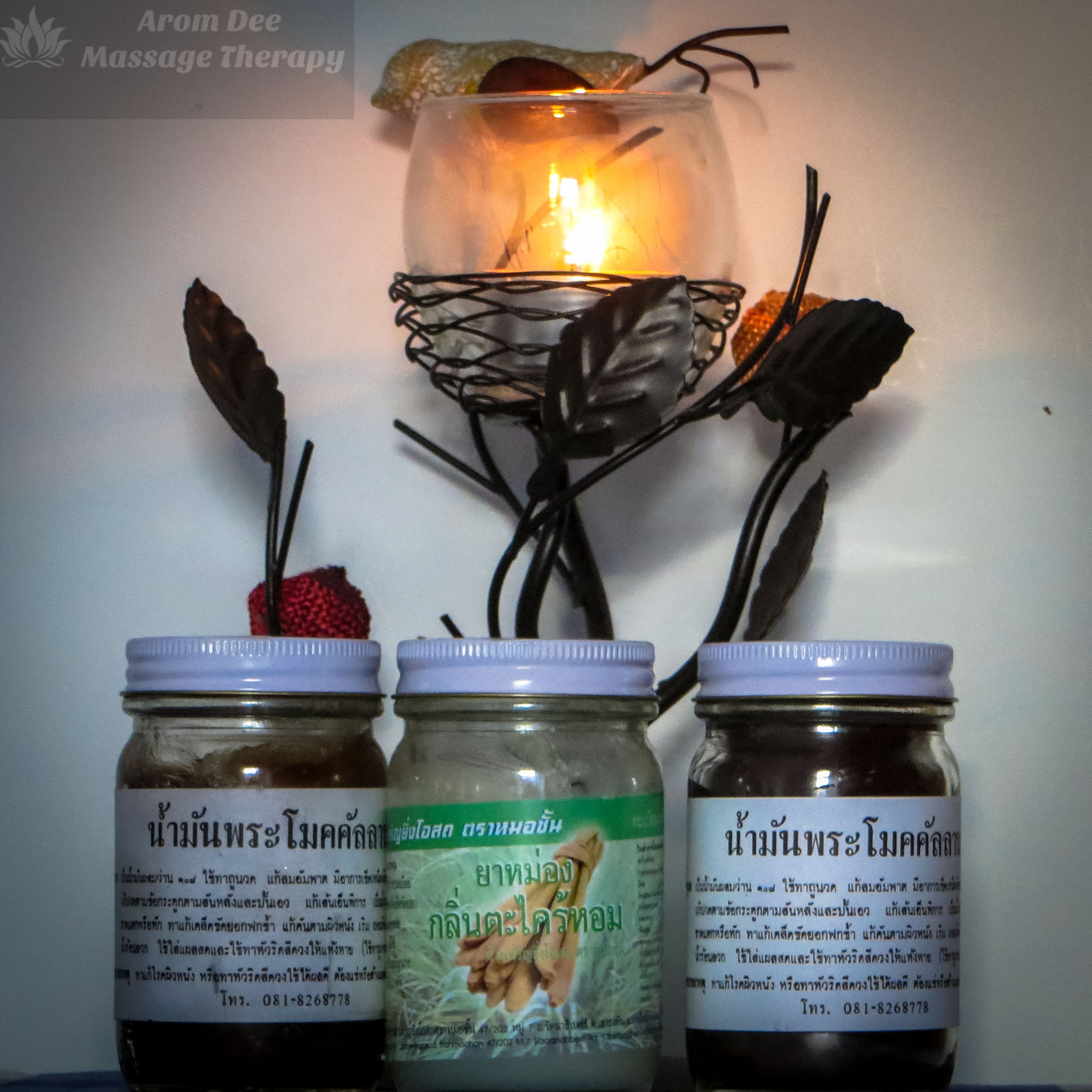 Three jars of Thai massage balm and candle