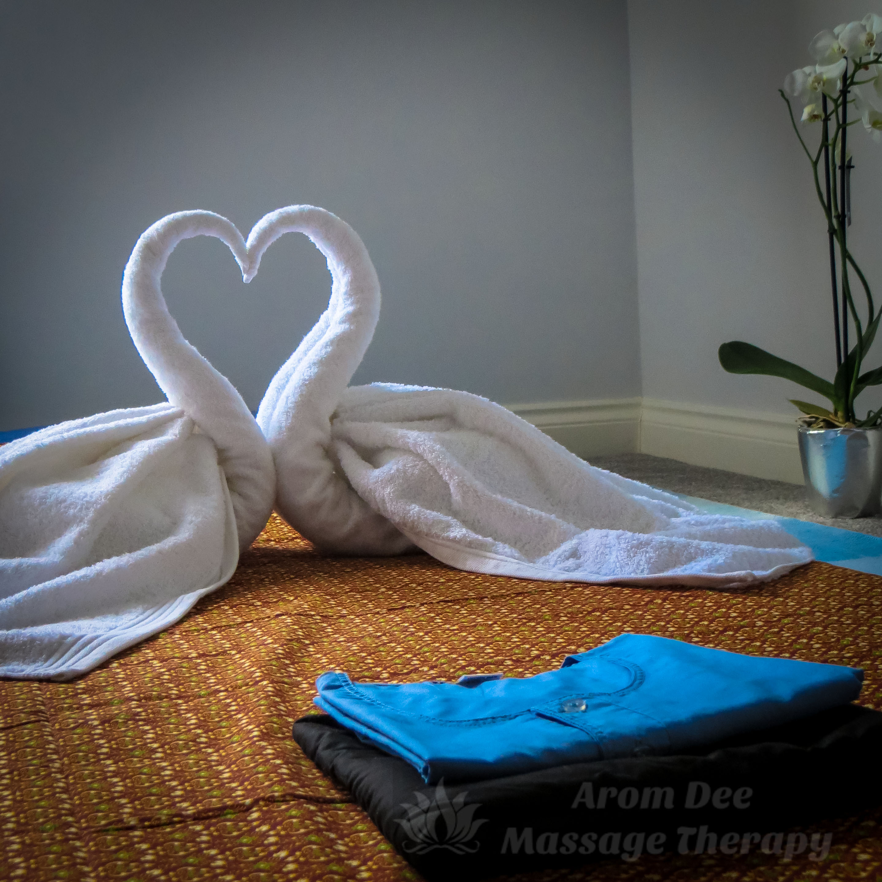 Folded client's Thai-style pyjamas in forground on floor pad with two white towels shaped into swans, their necks forming shape of a heart