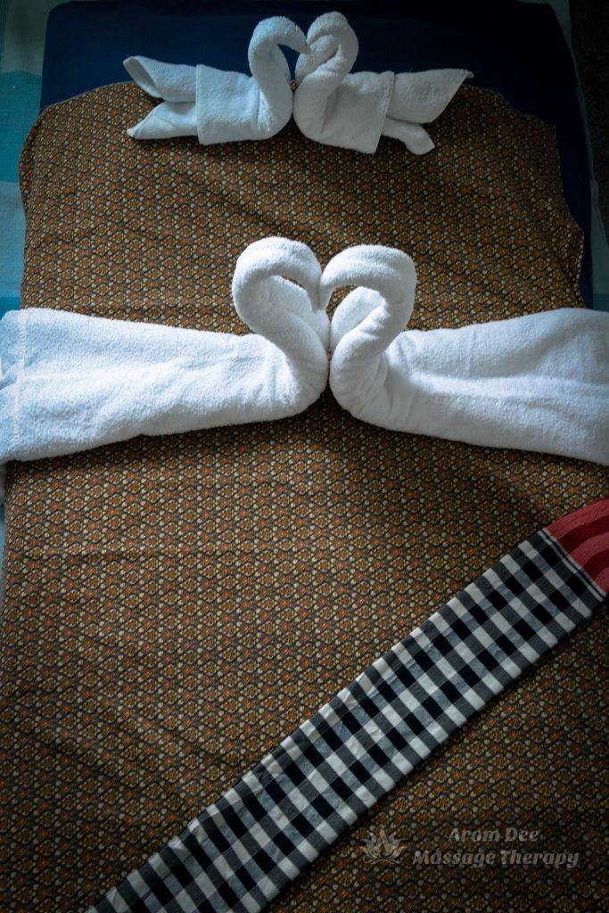 Towels folded intoTwo Swans in a Heart on Thai Massage Mat