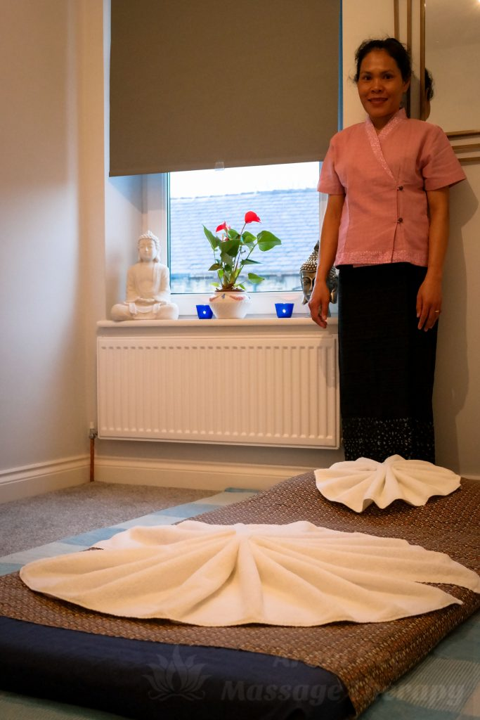 Thai masseuse wearing Isan style therapist uniform standing by mattress pad on floor