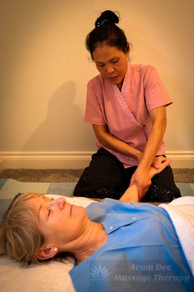 Masseuse in traditional Thai therapist's tunic applying pressure to client wearing Thai style pyjamas lying on mattress pad on floor