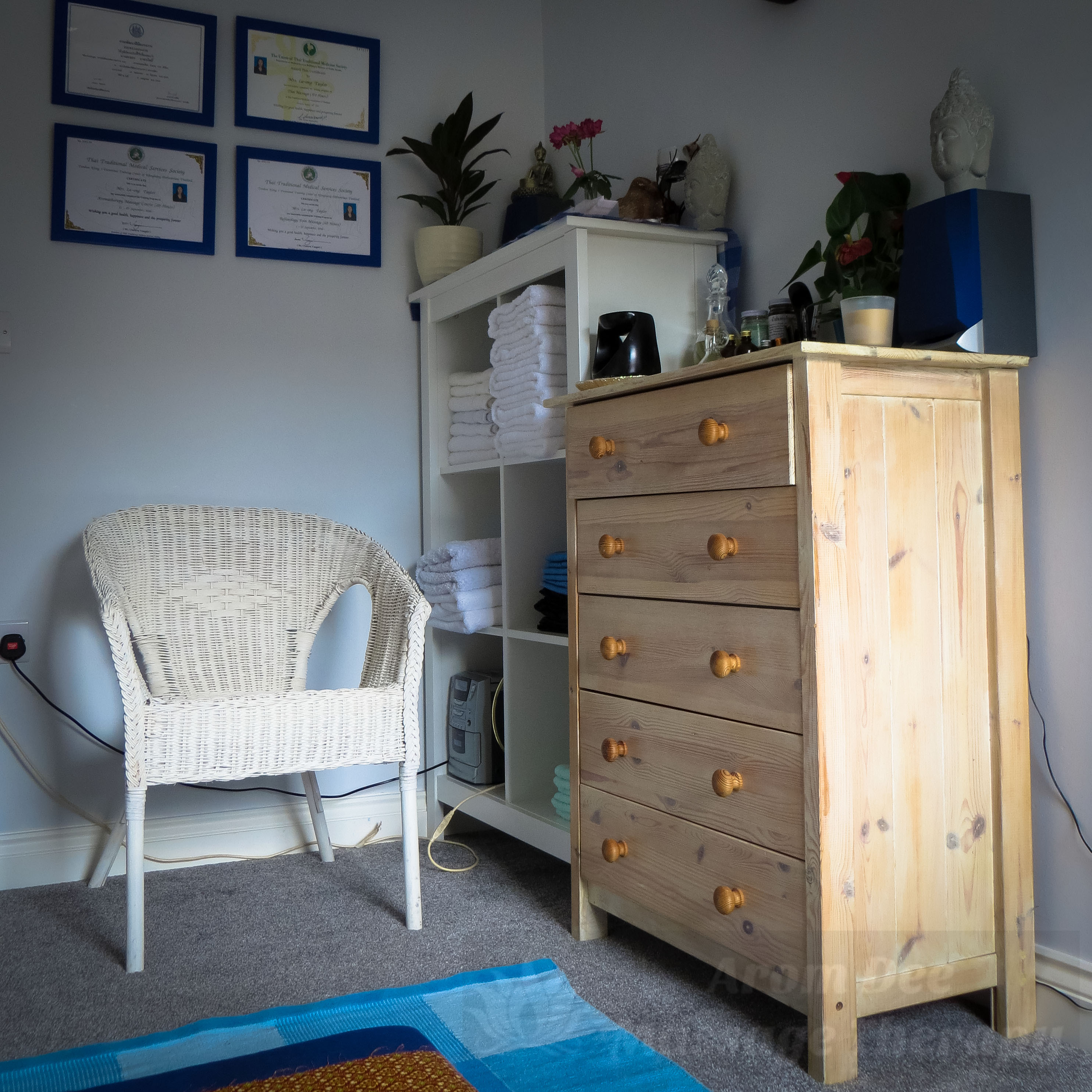 Four massage certificates on wall, chair, chest of drawers, folded towels inopen cabinet
