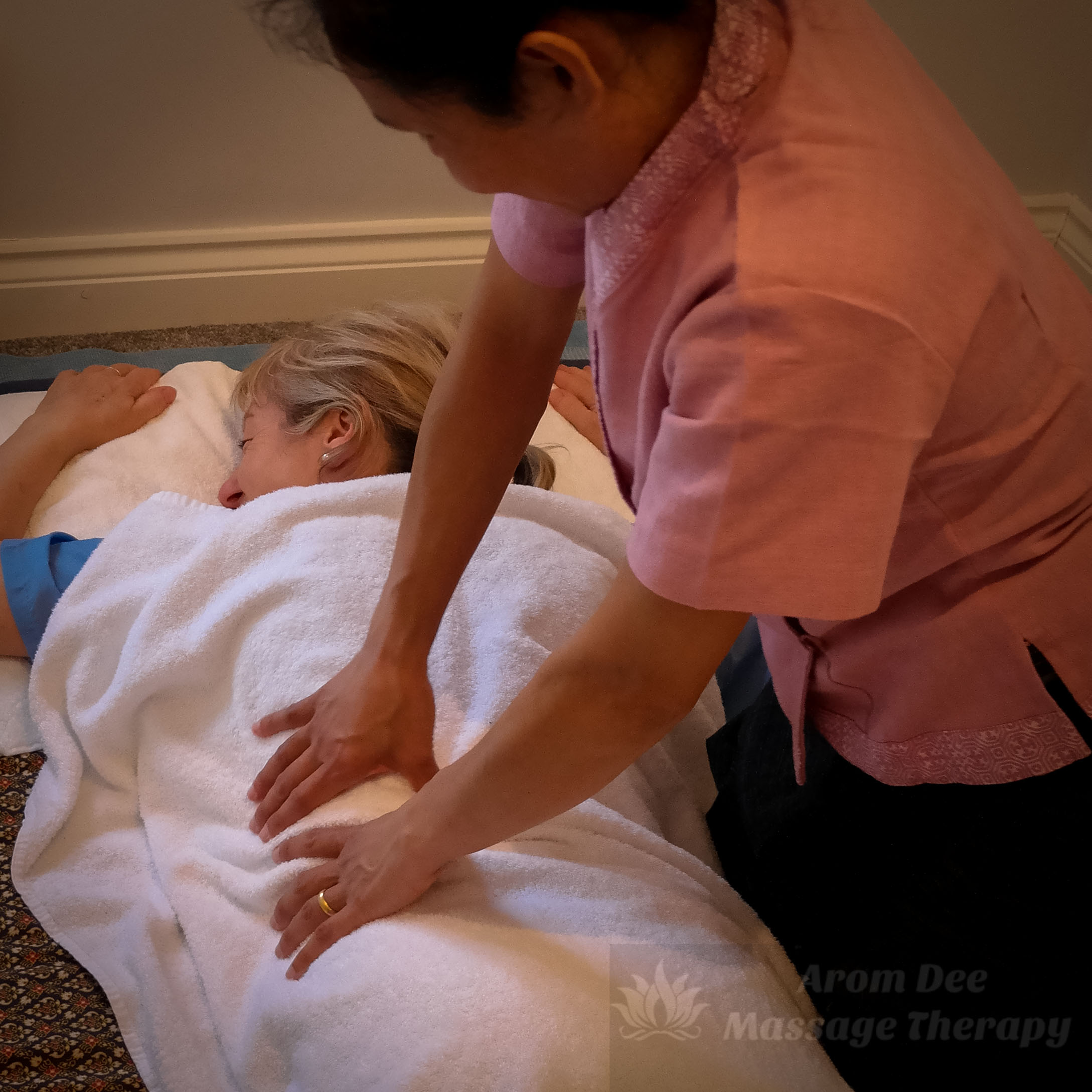 Accupressure applied to client's back through towel by masseuse