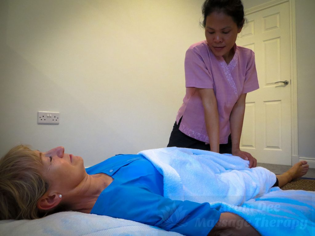 Masseuse wearing traditional Thai Therapist's top applying pressure to legs of client lying on mattress pad