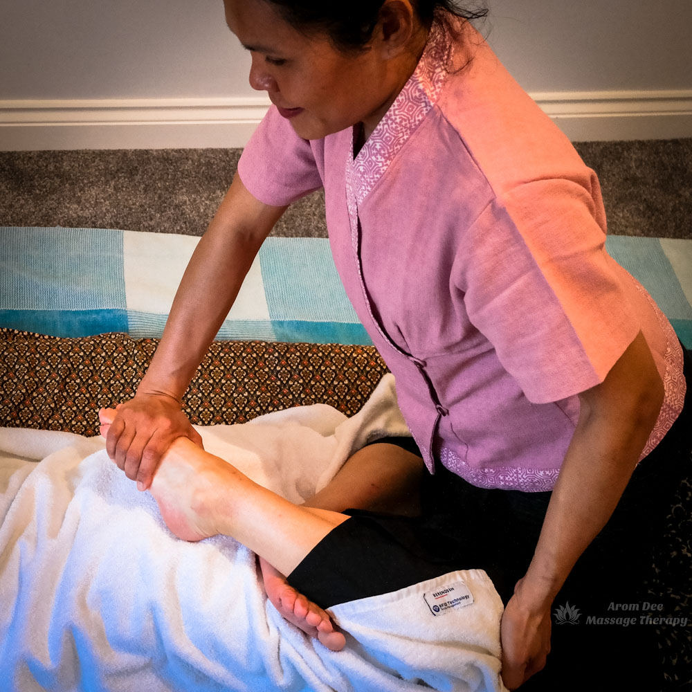 Female Thai therapist applying stretch technique to client lying on floor pad