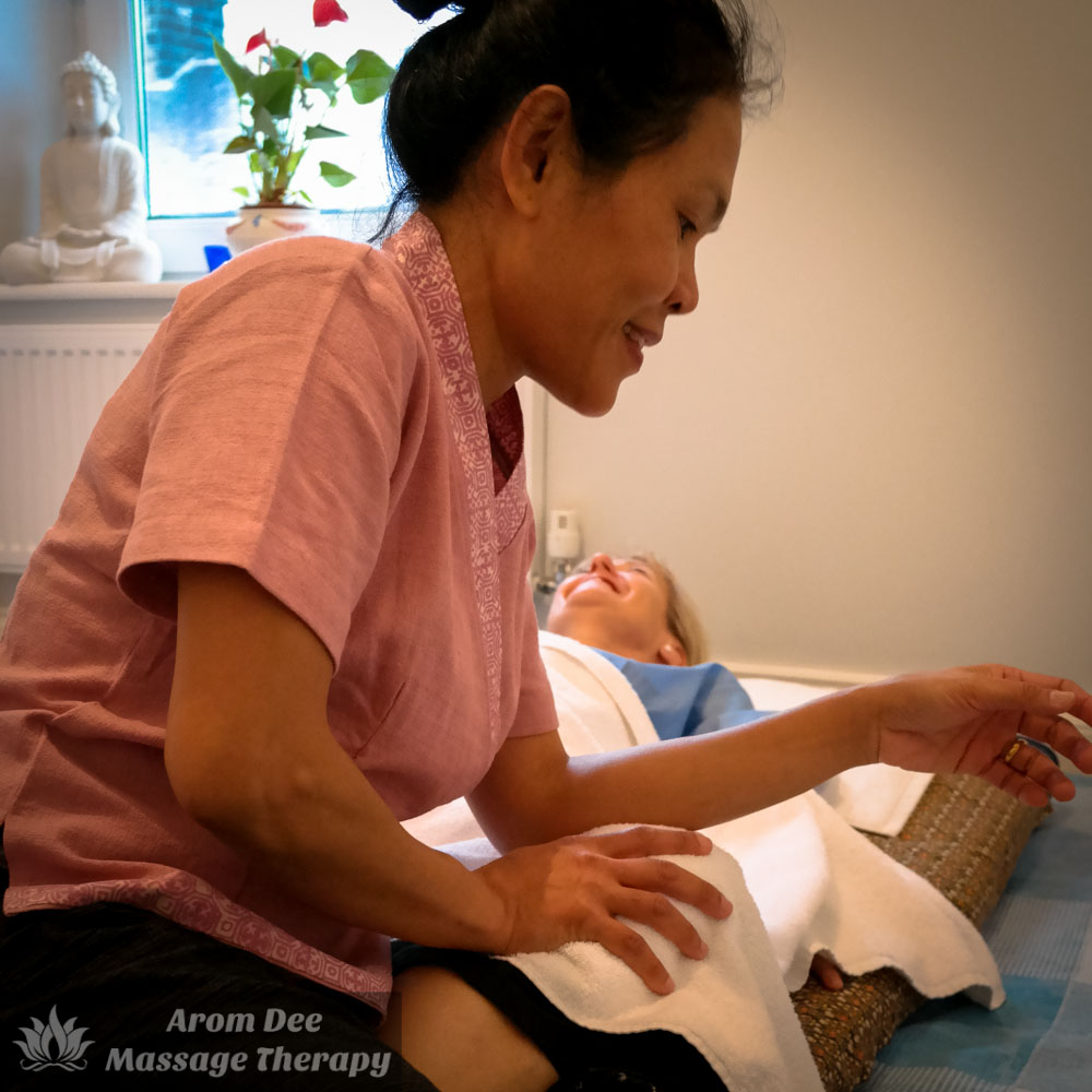 Female Thai massage therapist using her elbow to apply pressure to client on floor pad