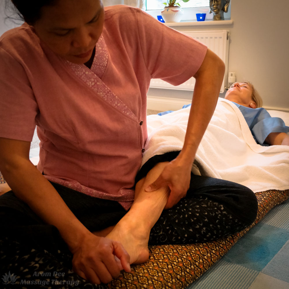 Female Thai massage therapist applying prssure with her left thum to client's leg