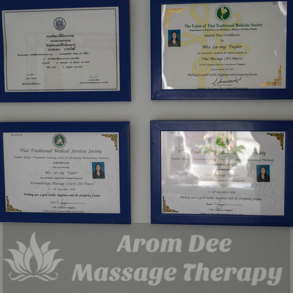 Four Thai Massage Certificates in blue frames on wall